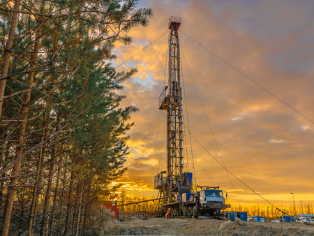 Drilling a deep well mobile drilling rig in an oil and gas field. The field is located in the Far North in the taiga. Beautiful dramatic sunset sky in the background. Stock Photo