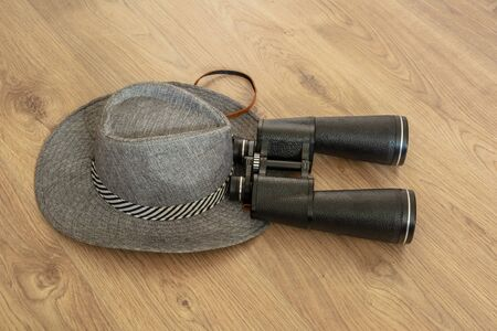 Wide-brimmed gray hat and binoculars, as symbols of travel. Wooden yellowish background. Preparation for the designer. Copy space.