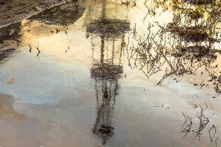 Reflection of blurred image of an oil rig in a puddle of oil. Dead plants.  The concept of environmental pollution when drilling for oil and gas. Ecology problems in oil and gas production.