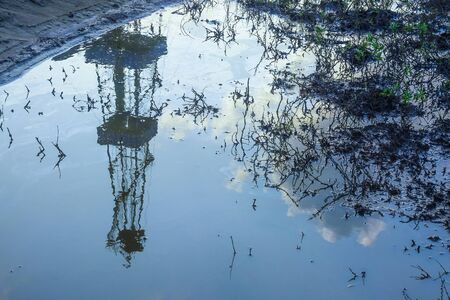 Reflection of blurred image of an oil rig in a puddle of oil. Dead plants. The concept of environmental pollution when drilling for oil and gas. Ecology problems in oil and gas production Banco de Imagens