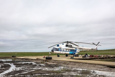 A polar aviation helicopter landed on a remote heliport in the northern tundra, not far from a drilling oil well. Wooden platform with lying equipment. Gloomy northern sky. Waiting for the arrival of drillers and oil workers.