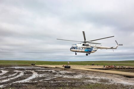 A polar aviation helicopter is preparing to land on a remote heliport in the northern tundra, not far from a drilling oil well. Wooden platform with lying equipment. Gloomy northern sky. The arrival of drillers and oil workers is expected.