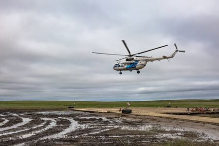 A polar aviation helicopter took off from a remote heliport in the northern tundra, not far from a drilling oil well. Wooden platform with lying equipment. Gloomy northern sky. A helicopter takes home drillers and oil workers. Banco de Imagens