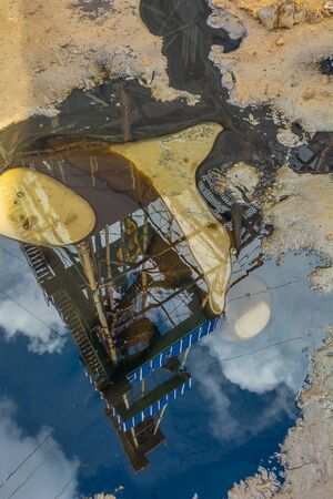 Drilling rig reflection in a puddle of oil. The concept of pollution of the Earths surface during oil and gas production Ecological disaster due to the activities of oil companies.