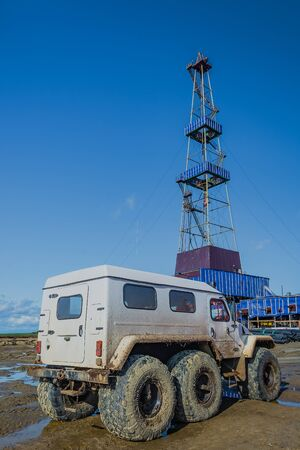 Off-road car with big wheels. White color. Dirty. In the background is a drilling rig. The concept of solving the transport problem in oil production in off-road conditions.