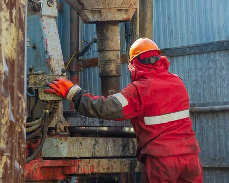 Work driller in red uniform, in helmet and goggles. He uses a hydraulic wrench to screw drill pipes to lower them into an oil well and continue drilling it. The concept of a working person.