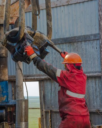 Gydan Peninsula  Russia - August 8 2019: Work driller in red uniform, in helmet and goggles. He with the help of an elevator hangs drill pipes to lift them from an oil well and continue its drilling. The concept of a working person. Banco de Imagens