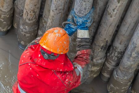 A working driller in a red uniform, in a helmet and goggles, installs drill pipes after lifting them from an oil well after drilling. The concept of a working person. Banco de Imagens