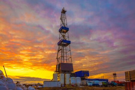 Drilling rig with a tower tower. Downstairs is the drilling equipment. A deep well is being drilled in the northern field for oil and gas production. Summer polar night. Beautiful sky with backlit clouds.
