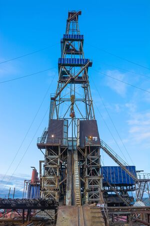 Drilling rig with a tower tower. Downstairs is the drilling equipment. A deep well is being drilled in the northern field for oil and gas production. Summer day. Blue cloudy sky. Banco de Imagens