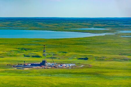 Drilling rig and equipment at an oil field in the northern tundra. Top view from a helicopter. Green summer tundra with lakes beyond the Arctic Circle. Banco de Imagens