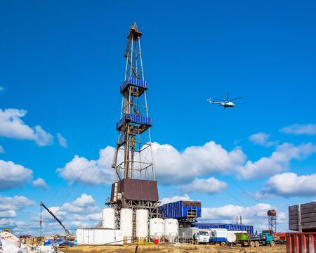 In the foreground is a drilling rig for drilling oil and gas wells with various equipment and materials. In the background is a flying helicopter. Summer sunny day on the field in the far north, in the Arctic. Beautiful sky.