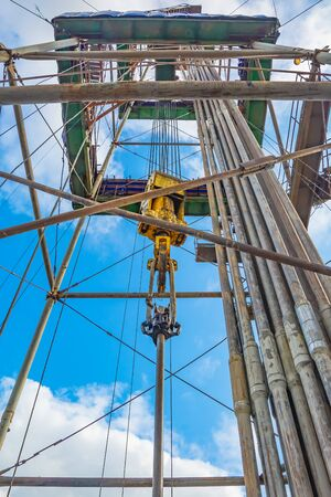 Location of equipment inside the oil and gas drilling rig. Drill pipes stand upright. Lifting system. View from bottom to top. Work is underway to raise drill pipes from the well.