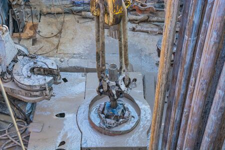 The location of the equipment inside the oil and gas drilling rig. In the center is a drill string suspended on an elevator and prepared for lifting from the well.