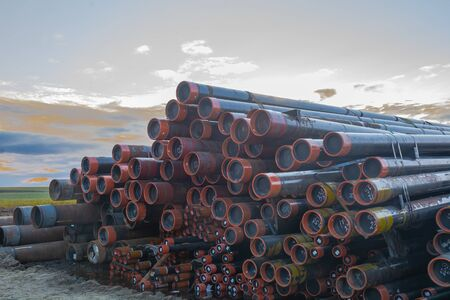 Casing pipes of different diameters are stored for storage. The threaded parts of the pipes are protected with plugs. The pipes are intended for lowering into oil and gas wells. The warehouse is located on the drilling site of an oil field in the tundra, in the North. Banco de Imagens
