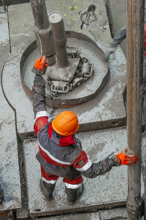 A working driller in a red uniform, in a helmet and goggles, installs drill pipes after lifting them from an oil well after drilling. The concept of a working person. Editorial