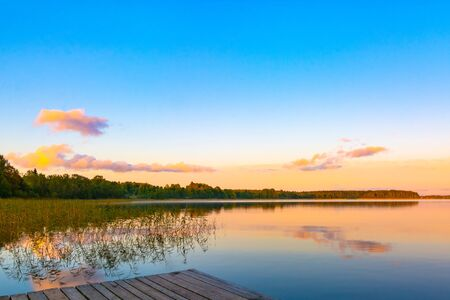 Summer evening on Lake Seliger. Beautiful sunset sky is reflected in the water. Thickets of reeds in the foreground. On the far shore is a forest. Rest and relaxation.