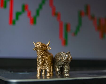 Bull and bear as symbols of stock trading on a blurred background of price graphics. The concept of symbolism of commodity and financial world markets.