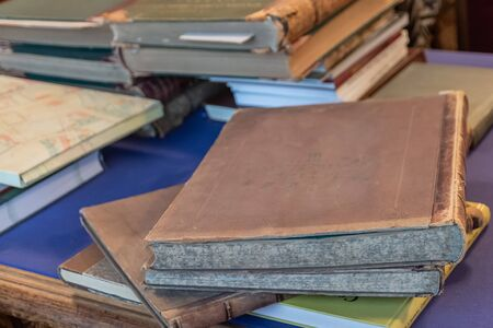 Shabby old books stacked in a pile on an old table with a fabric surface. Blurred background.