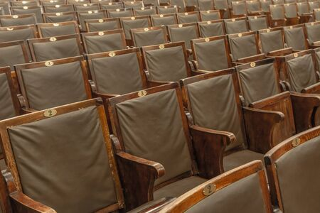 Antique wooden armchairs arranged in rows in a concert hall. Shabby surface, leather seats. Blurred image of chairs in the background.