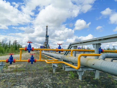 Pipeline fittings and manifold of producing gas wells in the field. Handwheels for high pressure valves. In the background, a drilling rig. Blurring distant objects.