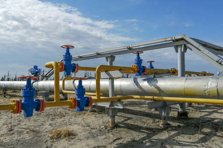Pipeline manifold of gas wells of producing gas wells in the northern field. High pressure gate valve handwheels, pipelines. In the background, a drilling rig. Blurring distant objects. 免版税图像