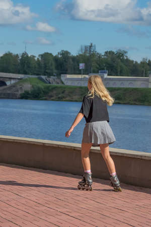 A young girl with blond hair, in a black T-shirt and a plaid skirt, is rollerblading along the city embankment on a summer day. The cityscape in the background is blurred.