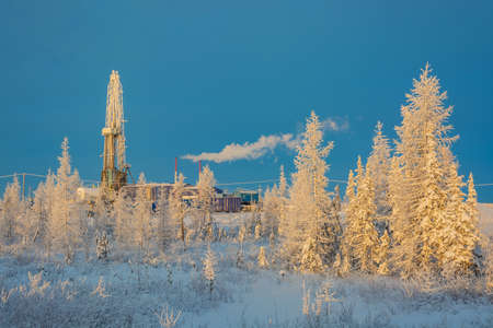 Drilling rig in a taiga forest at the northern field. Landscape in the rays of the rising sun on a polar winter day. Everything is covered with snow with a yellow tint in reflected light Banque d'images