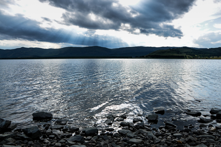 Mountain lake in Ural, Russia. Gloomy sky, the rays of the sun