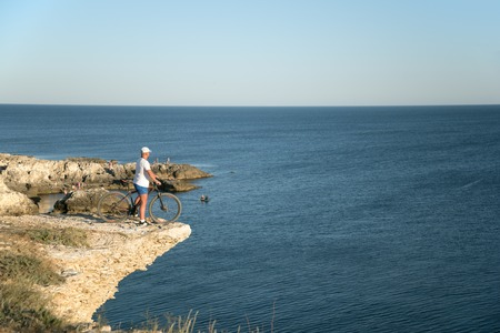 The man with the bike on the rocky shore of the sea watching the horizont Stock Photo