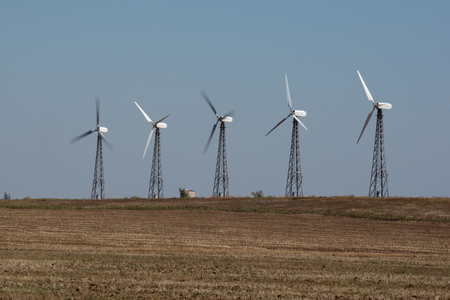 Rotating power saving windmills built on dried field in rural environment.