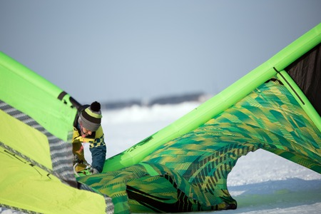 The athlete in the winter is preparing a green kite for Snowkiting on the snowy field Stock Photo