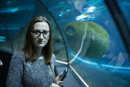 Young woman with smartphone standing at the tank and looking at camera.