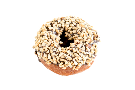 Donut covered with chocolate and sprinkled with crushed nuts on white isolate background Imagens