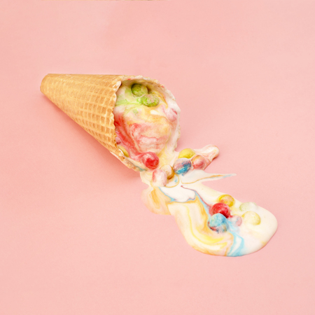 Ice cream in waffle cone with multicolored candies in filling melted on pink background