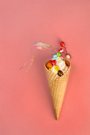 Ice cream in waffle cone with multicolored candies in filling smeared on pink background