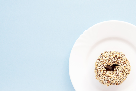 Donut covered with chocolate glaze and sprinkled with nuts on white plates on a blue table Imagens