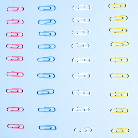 Multi-colored paper clips in row on blue background