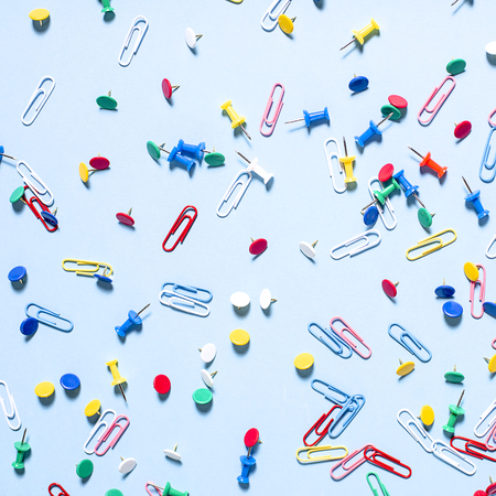 Office supplies in the form of colored buttons and paper clips on blue background