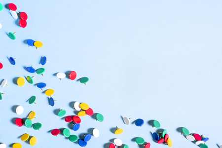 Multi-colored stationery buttons with needles on blue background in corner