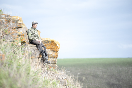 A man in uniform sitting on a rock on a mountainside on a summer day and looking into the distance