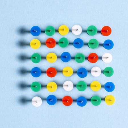 Multi-colored stationery buttons on a blue background stacked needles up in a row Stock Photo