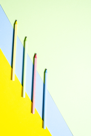 Multi-colored striped beautiful pencils in tri-color background yellow, blue and green