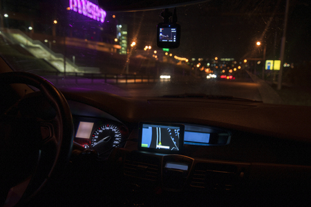Navigator installed in the car. The car is in the night city and the lights of the night city are lit. Фото со стока