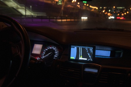 Navigator panel of the car at night. The city lights are burning from street lighting.