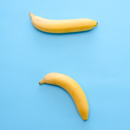 Composition of yellow bananas on a blue background to display problems with the potency of men