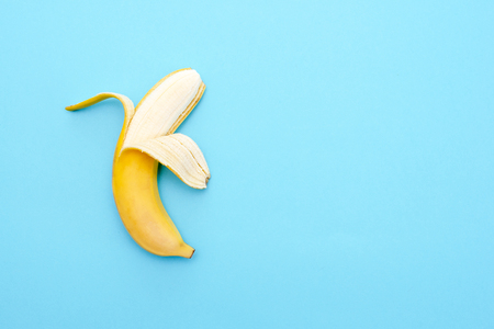 Yellow ripe banana peeled half on blue surface Stock Photo
