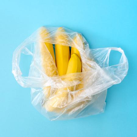 Yellow ripe fresh bananas in transparent plastic bag on blue background