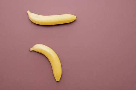 Composition of yellow bananas on a brown background to display problems with the potency of men Stock Photo
