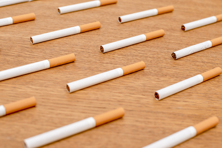 White cigarettes with orange filter lined in a row in order on a wooden background